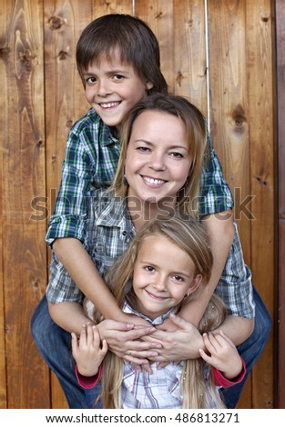 Family portrait against wooden wall - woman and kids smiling happily