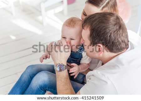 family portrait father mother and son in white shirts and blue jeans dad playing with his son dragged him by the nose - stock photo