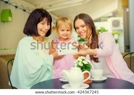 Family portrait in cafe. Aged woman with adult daughter and little granddaughter taking selfie together. - stock photo