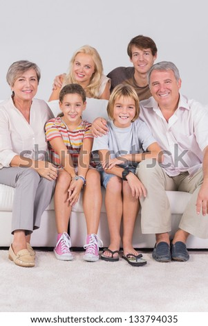 Family portrait looking at camera in sitting room - stock photo