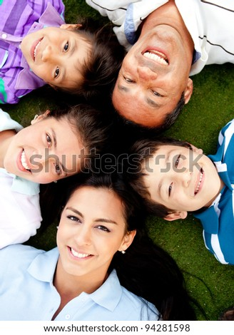 Family portrait lying on the floor with their heads together - stock photo