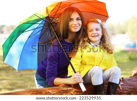 Family portrait mother and child with colorful umbrella having fun enjoying weather in autumn day - stock photo