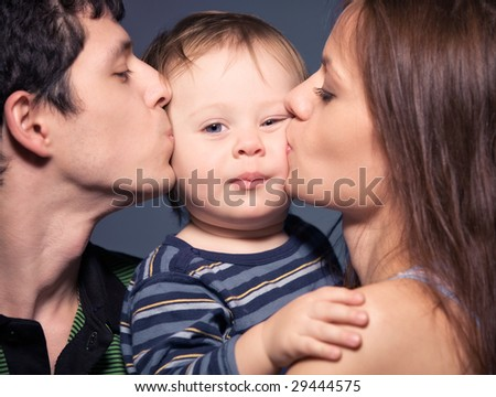 Family portrait. Mother and father kissing their son. - stock photo
