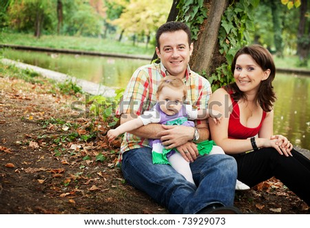 Family portrait - mother father and baby daughter outdoor - stock photo