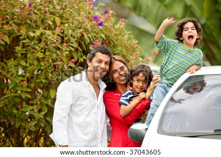 Family portrait next to a car outdoors - stock photo