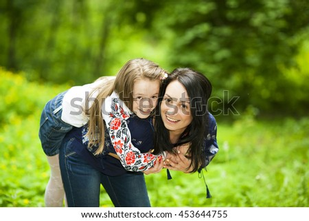 Family portrait of a happy girl and mother in the park on a background of green trees - stock photo