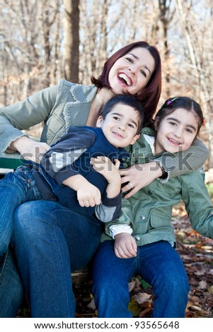 Family portrait of a happy laughing mother hugging smiling boy and girl. - stock photo