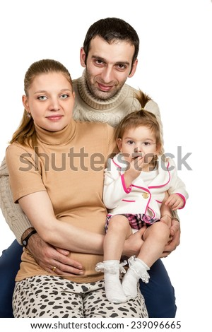 Family portrait of a pregnant mother father and daughter who eats candy isolated on white background - stock photo