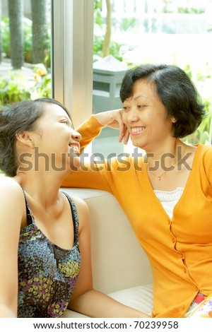 Family portrait of Asian ethnic mature mother enjoy talking with teen daughter