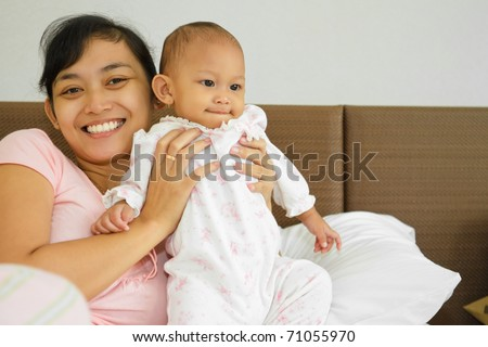 Family portrait of asian ethnic mother holding cute baby girl on bed