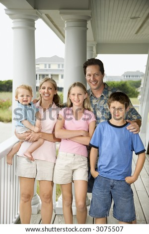 Family portrait of Caucasian mid-adult man and woman with pre-teen girl and boy and male toddler, standing on porch. - stock photo