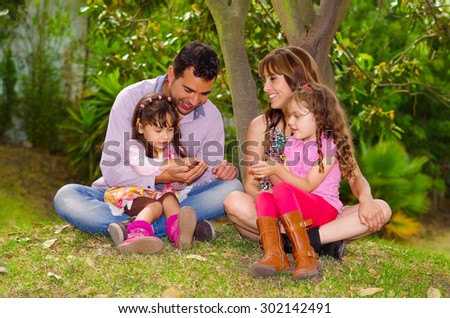 Family portrait of father, mother and two daughters sitting together in garden environment enjoying each others company .