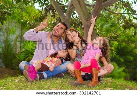 Family portrait of father, mother and two daughters sitting together in garden environment pointing looking upwards towards the sky. - stock photo