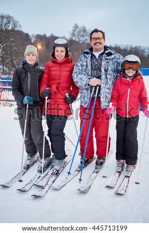 Family portrait of four skiers standing at ski resort in evening.