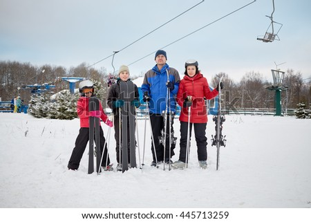 Family portrait of four skiers standing with skis at ski resort.