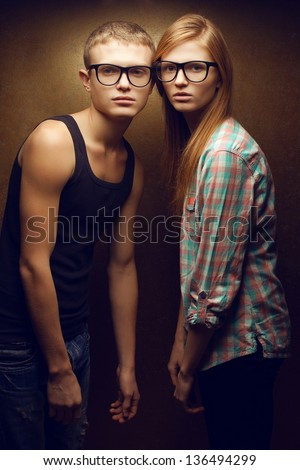 Family portrait of gorgeous red-haired fashion twins in casual shirts wearing trendy glasses and posing over golden background together. Hipster style. Studio shot. - stock photo
