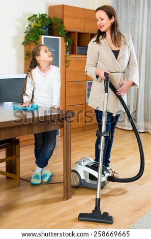 Family portrait of happy girl helping mom to clean room - stock photo
