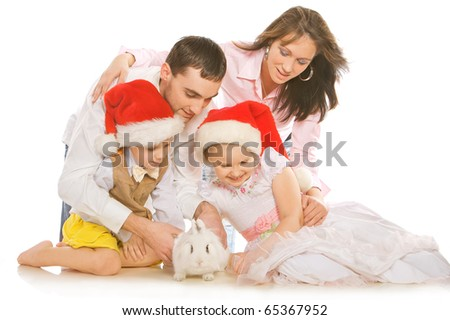 Family portrait of happy parents and children with white bunny.