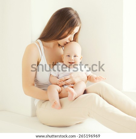 Family portrait of happy young mother kissing cute baby at home in white room near window - stock photo