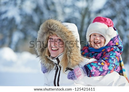Family portrait of happy young woman mother with little child girl daughter and in winter outdoors - stock photo