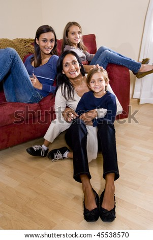 Family portrait of Indian mother with 3 mixed-race children sitting at home together on sofa - stock photo