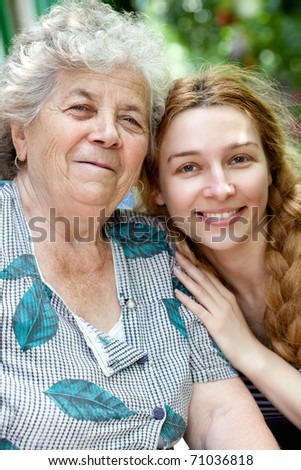 Family portrait of joyful young woman and her grandmother