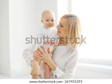 Family portrait of mother and baby together at home in white room near window - stock photo