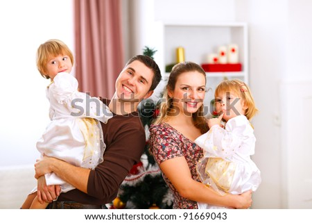 Family portrait of mother father and twins daughter near Christmas tree