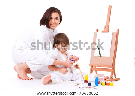 Family portrait of son and mom dressed in white painting near easel