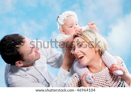 Family portrait of the beautiful happy couple with the small child  astride  shoulders - stock photo