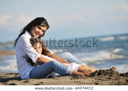 family portrait of young beautiful mom and daughter on beach - stock photo