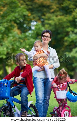 Family portrait outdoor in park. Modern mom with kids. Child learning to ride bike