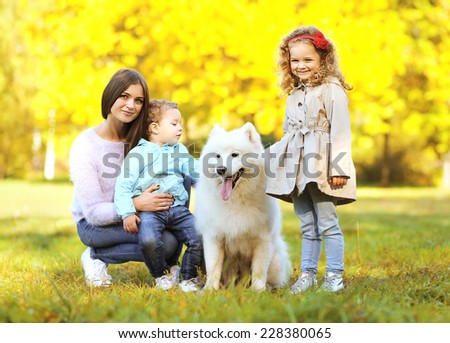 Family portrait, pretty young mother and children walks with dog outdoors in the park - stock photo