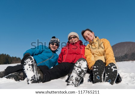 Family portrait - senior man and woman with their adult daughter in winter - sitting in snow