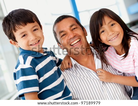 Family portrait with father holding his two kids