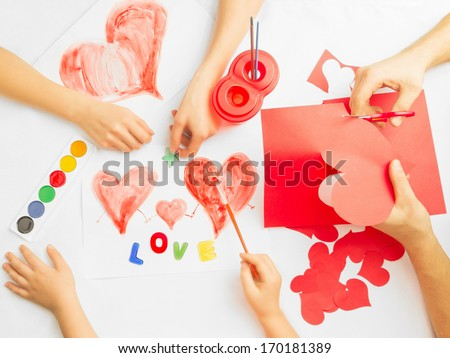 Family prepare for Valentine's Day. Paintings and origami of heart. Concept of family. Point of view shot - stock photo