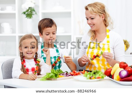 Family preparing a fresh vegetables meal together in the kitchen - stock photo
