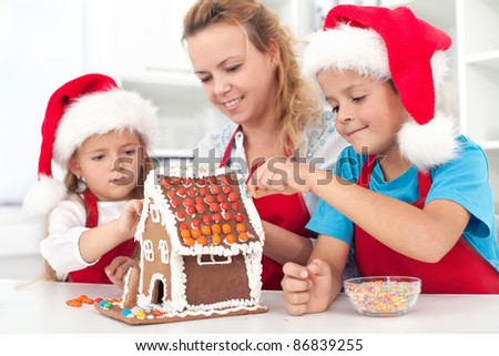 Family preparing a gingerbread cookie house at christmas time