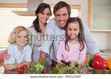 Family preparing a salad in a kitchen - stock photo