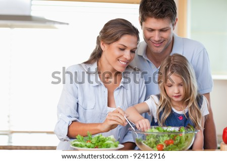 Family preparing a salad in their kitchen - stock photo