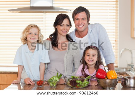 Family preparing a salad together in a kitchen - stock photo