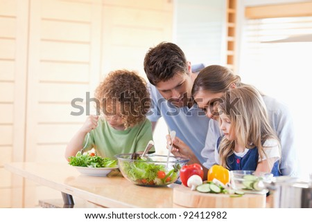 Family preparing a salad together in their kitchen - stock photo