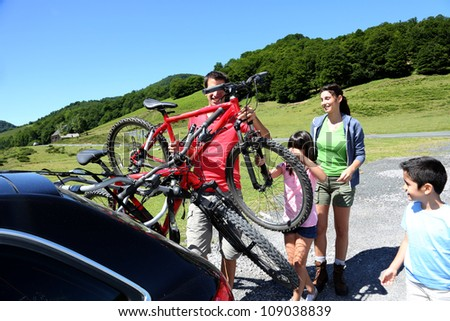 Family preparing bicycles for recreational journey - stock photo