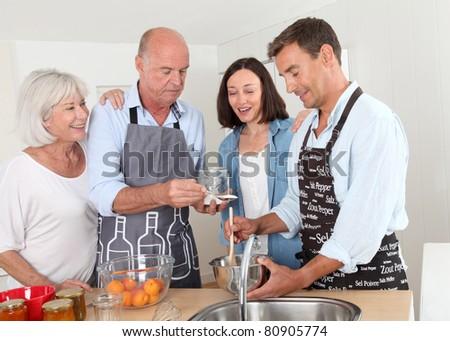 Family preparing fruit jam in home kitchen - stock photo
