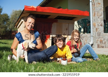 Family preparing the doghouse for the new family member - a labrador puppy - stock photo