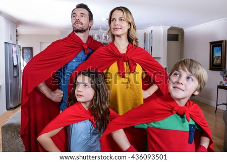 Family pretending to be superhero in living room at home - stock photo