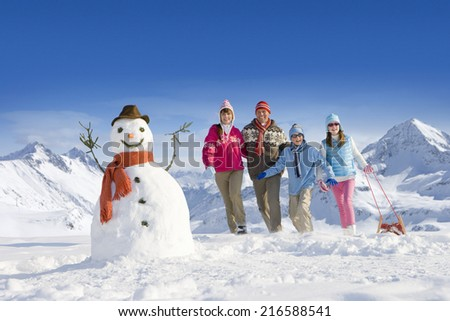 Family puling sled towards snowman - stock photo