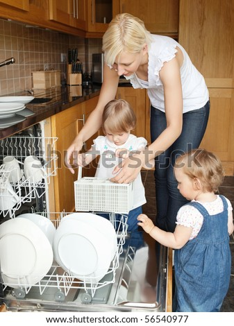 Family put dishes in the dishwasher in the kitchen - stock photo