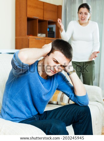 Family quarrel. Sad guy against aggressive wife at home - stock photo