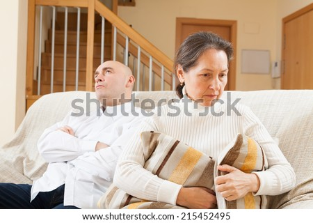 Family quarrel. Sad guy and woman during conflict in living room at home